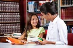 看起来女性图书管理员的愉快的女小学生  免版税库存照片