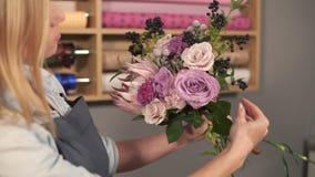 看起来女性白肤金发的卖花人侧视图安排现代花束和花怎么被结合 英俊的花 股票录像