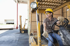 看起来女性的产业工人去,当驾驶叉架起货车时 库存图片
