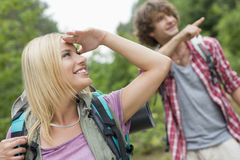 看起来女性的背包徒步旅行者去,当显示某事的人在森林时 库存图片