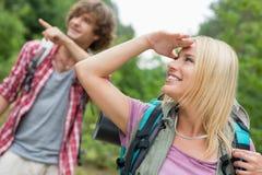 看起来女性的背包徒步旅行者去,当显示某事的人在森林时 免版税库存照片