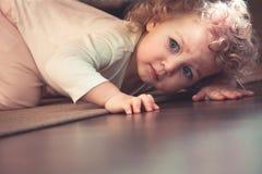 看起来好奇逗人喜爱的孩子掩藏在床下在孩子屋子里和惊吓 库存照片