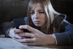 看起来少年的女孩担心和绝望对手机,互联网偷偷了靠近受害者被滥用的cyberbullying的重音 库存图片