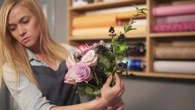看起来年轻女性白肤金发的卖花人安排现代花束和花怎么被结合 英俊的花店 影视素材