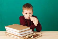看起来年轻的男孩恼怒摇他的拳头疲倦了于学校教训 免版税库存照片