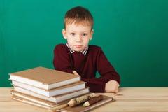 看起来年轻的男孩恼怒摇他的拳头疲倦了于学校教训 库存照片