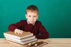 看起来年轻的男孩恼怒摇他的拳头疲倦了于学校教训 库存图片
