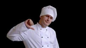 看起来年轻英俊的厨师的人不快乐和恼怒的显示的拒绝和阴性与拇指在姿态下 被证章的 股票录像