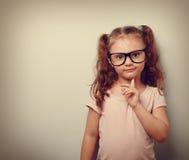 看起来想法的逗人喜爱的孩子的女孩确信对镜片 葡萄酒 免版税库存照片