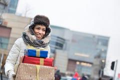 看起来愉快的妇女去,当运载被堆积的礼物在冬天期间时 免版税库存照片