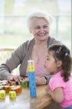 看起来愉快的祖母去,当吹被堆积的字母表块的孙女在房子里时 免版税库存照片