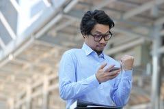 看起来流动巧妙的电话和举手的成功的年轻亚裔商人在都市城市背景 库存图片