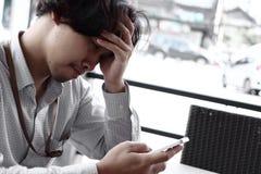 看起来流动巧妙的电话的担心的沮丧的年轻亚洲商人 忧虑企业概念 库存照片