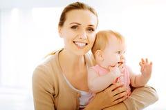 看起来爱恋的母亲愉快,当是以她的婴孩时 免版税图库摄影