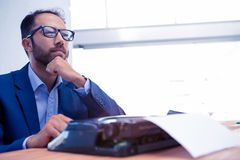 看起来的商人去,当工作在打字机时 免版税库存照片
