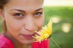 看起来的妇女向上,当嗅到一朵黄色花时 库存图片