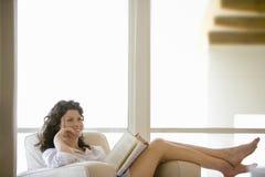 看起来的妇女去,当放松在扶手椅子时 免版税库存照片