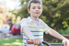 看起来的自行车的男孩严肃 库存图片