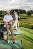 看起来的高尔夫球运动员去,当打高尔夫球时的朋友 库存照片
