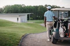 看起来的高尔夫球运动员去,当站立近的高尔夫车时 免版税库存照片