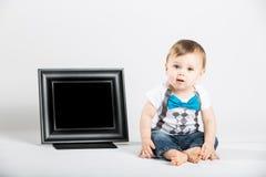 看起来的婴孩坐在画框旁边和感兴趣 库存照片