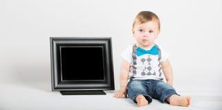 看起来的婴孩坐在画框旁边和混淆 免版税库存照片