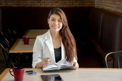 看起来确信工作在与书和片剂的咖啡店的微笑的成功的现代亚裔女商人 免版税库存图片