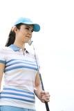 看起来确信的妇女去,当拿着高尔夫俱乐部反对清楚的天空时 库存图片