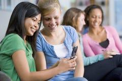 看起来移动电话的女孩少年 免版税库存图片