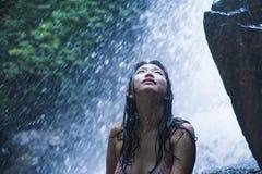 看起来纯净和享受自然秀丽用面孔湿下面惊人的美丽的自然水的年轻美丽的亚裔女孩画象  免版税库存图片