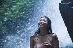 看起来纯净和享受自然秀丽用面孔湿下面惊人的美丽的自然水的年轻美丽的亚裔女孩画象  图库摄影