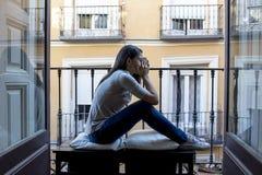 看起来绝望哀伤的拉丁妇女在家的阳台被摧残的和沮丧的遭受的消沉 库存照片
