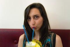 看起来美丽的女孩喝鸡尾酒和直接 免版税库存照片