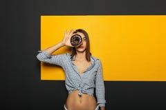 看起来美丽的女孩好奇通过多福饼对照相机 免版税库存图片