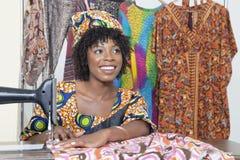看起来美丽的非裔美国人的女性的裁缝去,当缝在缝纫机时的布料 免版税库存图片