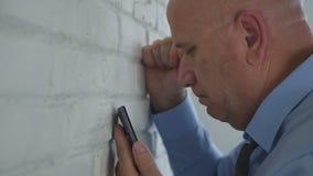 看起来翻倒的商人失望在手机消息 库存照片
