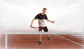 看起来英俊的年轻的人拿着网球拍和去,当时 库存照片