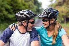 看起来运动的夫妇面对面,当骑自行车时 库存照片