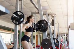 看起来适合年轻女人举的杠铃聚焦,解决在健身房,加强有模拟器的肌肉,有训练的力量 免版税库存照片