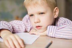 看起来逗人喜爱的男孩做他的家庭作业和疲乏 免版税库存照片