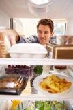 看起来里面冰箱的人充满食物 图库摄影