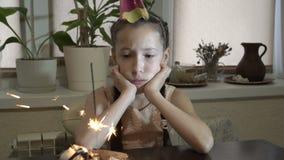 看起来闪烁发光物一哀伤的女孩的画象烧毁 她坐在休息他的蛋糕前面的一张桌上 影视素材