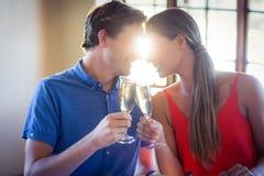 看起来面对面和敬酒香槟槽的年轻夫妇 免版税图库摄影