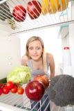 看起来食物的冰箱青少年 免版税库存图片
