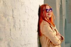 看起来去愉快的Redhair妇女 摆在便衣和时兴的第60副样式太阳镜的白色砖墙附近的时髦女孩 图库摄影