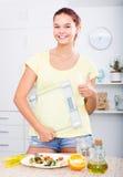 看起来满意和拿着在厨房的少年女孩标度 库存照片