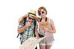 看起来年轻旅游夫妇读书城市的地图与女孩运载的旅行背包丢失和混淆疏松取向 免版税库存照片
