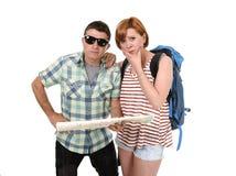 看起来年轻旅游夫妇读书城市的地图与女孩运载的旅行背包丢失和混淆疏松取向 库存照片
