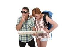 看起来年轻旅游夫妇读书城市的地图与女孩运载的旅行背包丢失和混淆疏松取向 库存图片