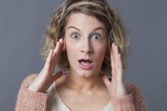 看起来年轻白肤金发的妇女震惊 免版税库存图片